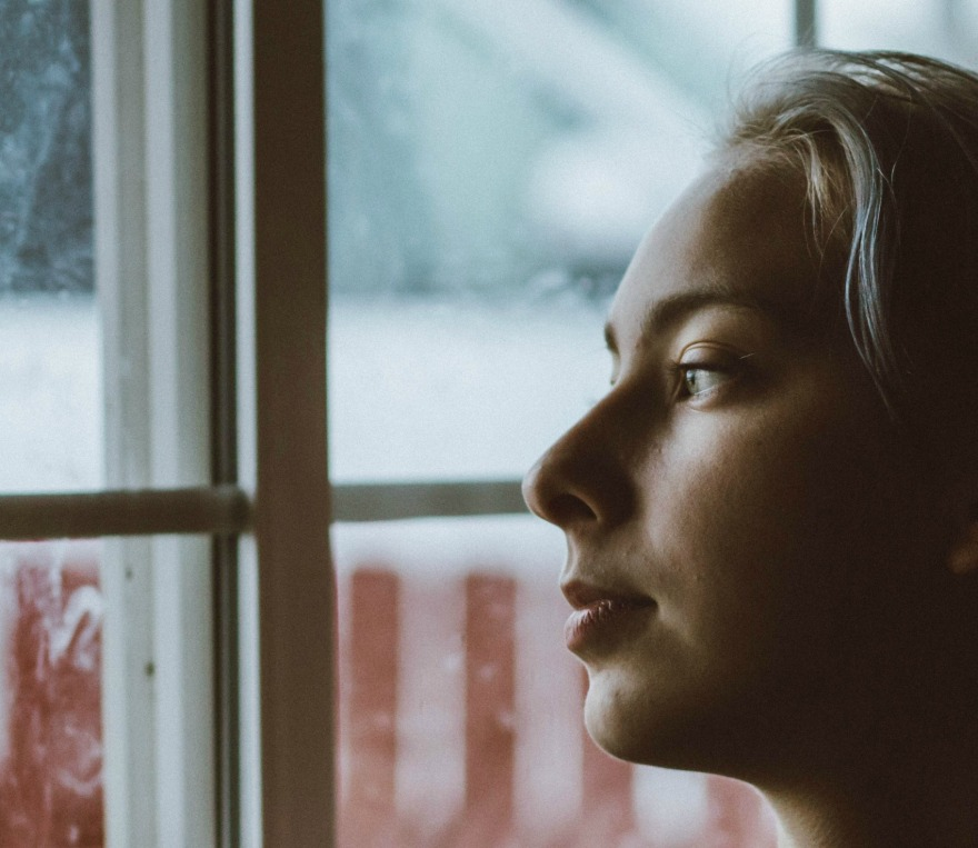 woman staring out a window